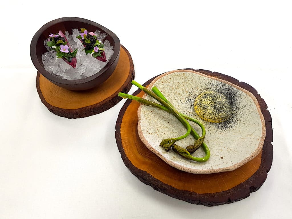 two small plates of foraged food presented on a white tablecloth and wooden disks