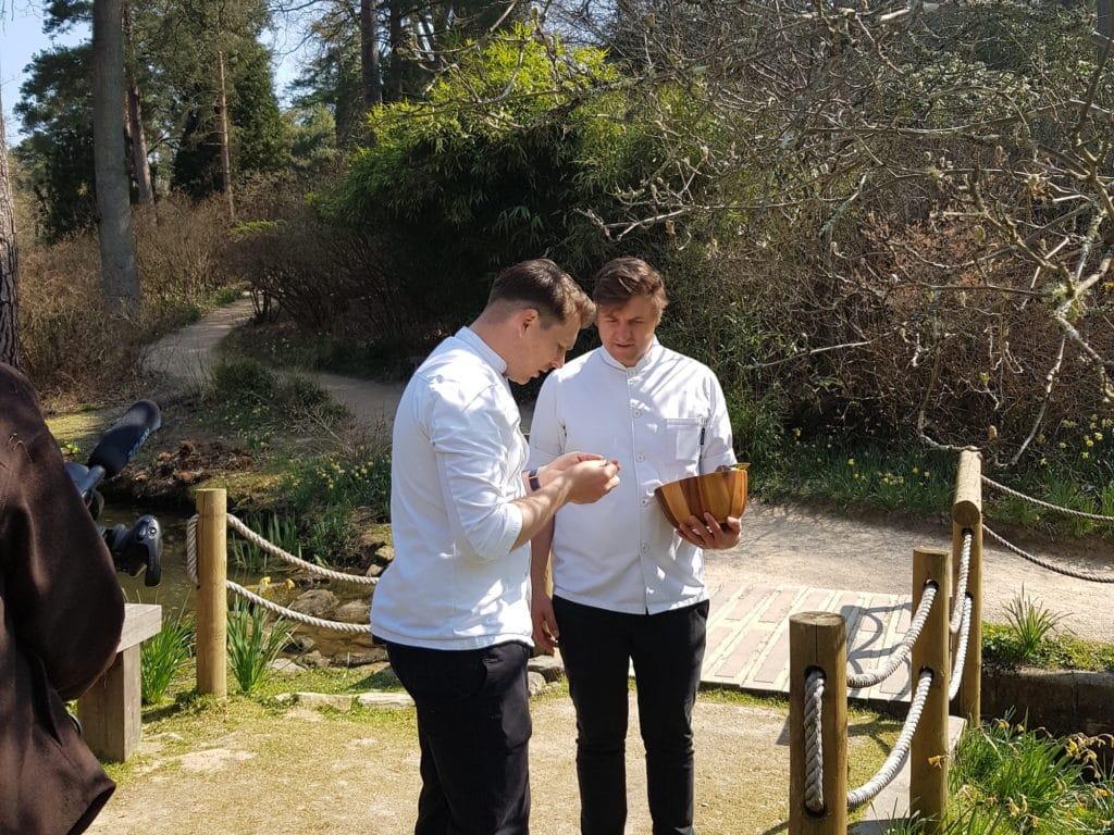 Chefs stood on a bridge holding foraged ingredients