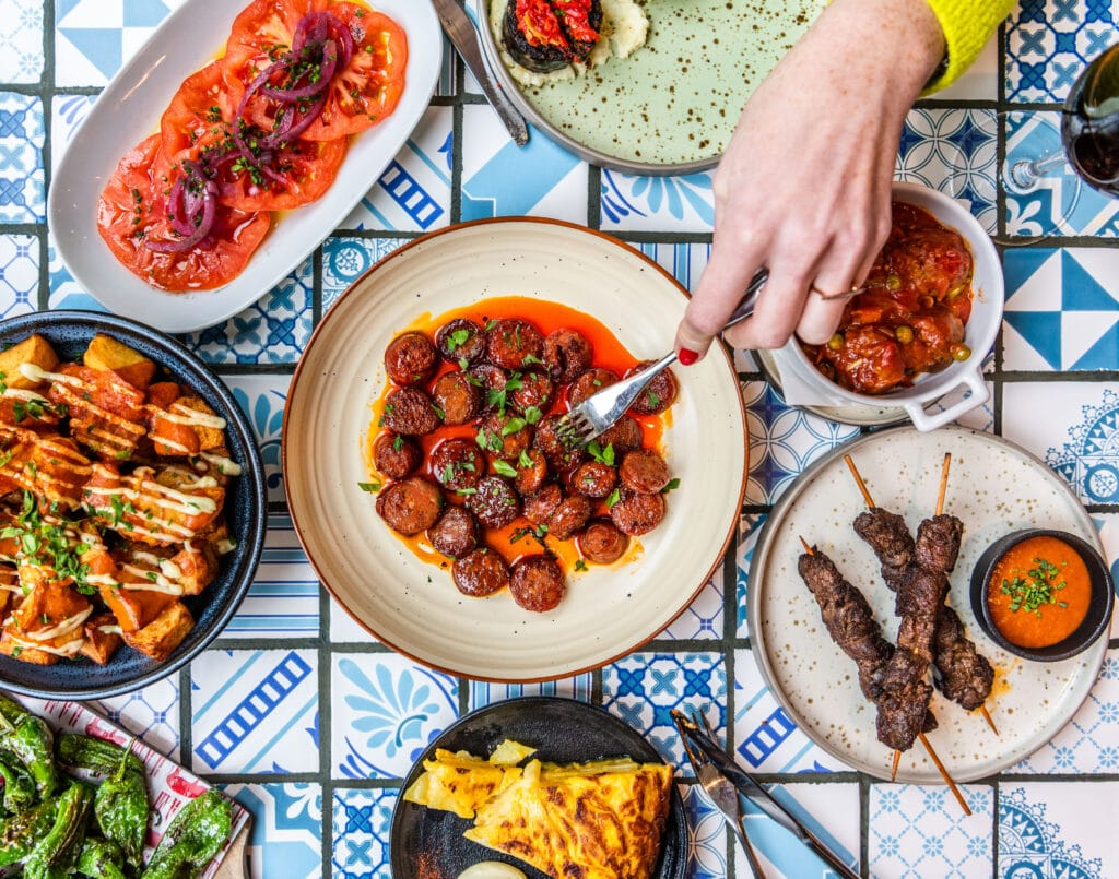 Tapas plates - overhead shot with hand reaching in with a fork