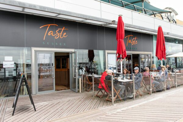 outside of taste sussex restaurant, people seating at their tables