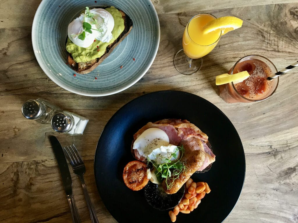 Bacon, egg and tomato alongside a plate of avocado on toast with a poached egg. Served with juice on a rustic wooden table.