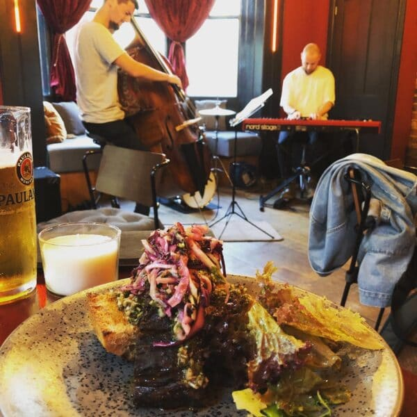 Brisket served with glass of beer and jazz singer in backgroud