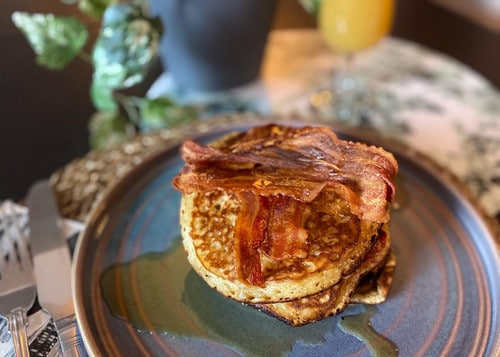 A blue plate with a stack of pancakes, crispy bacon and maple syrup