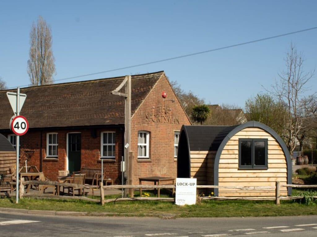A red brick classic country pub with a wooden dining cabin at the front