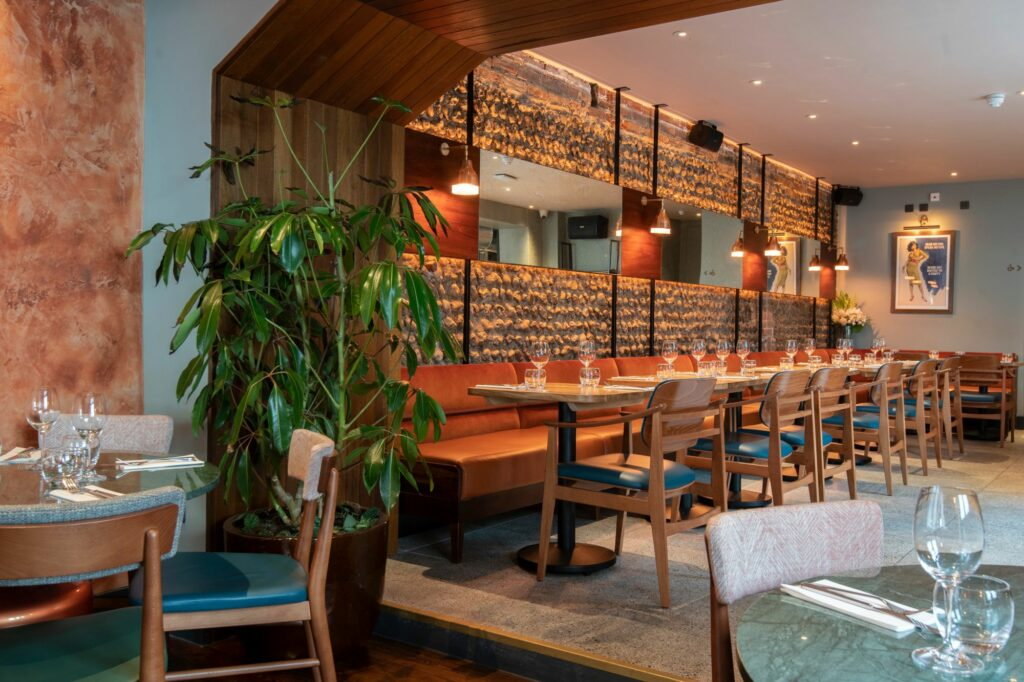 interior of new Brightons restaurant, brown walls decorated with wood and rock, brown tables and loung sofa, brown chairs with dark green seats