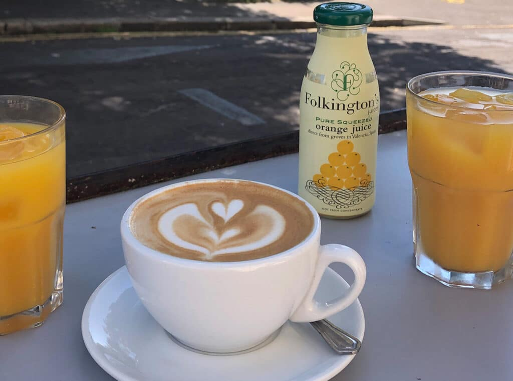 A cup of coffee with cappuccino art and two glasses of orange juice.