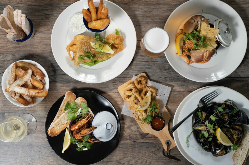 table laid with four different dishes including fish and chips, mussels, prawns, lobster and onion rings as side dish