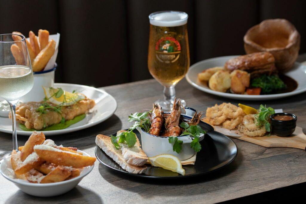 table laid out with few dishes but camera focuse on prawns with chips and bread, beer served as a drink