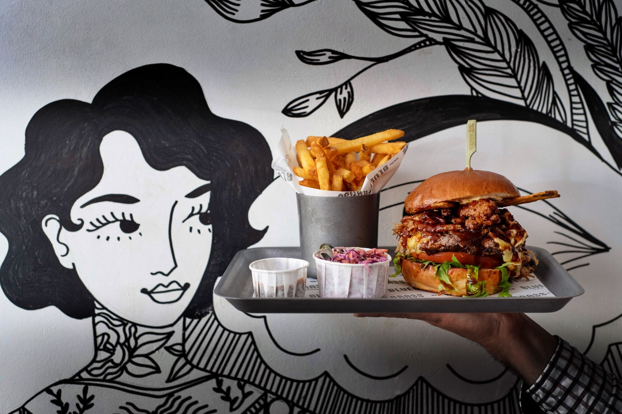 burger and chips on tray with mural in background