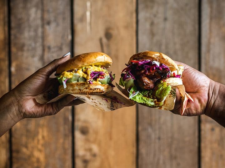 two hands facing, each holding meat burgers
