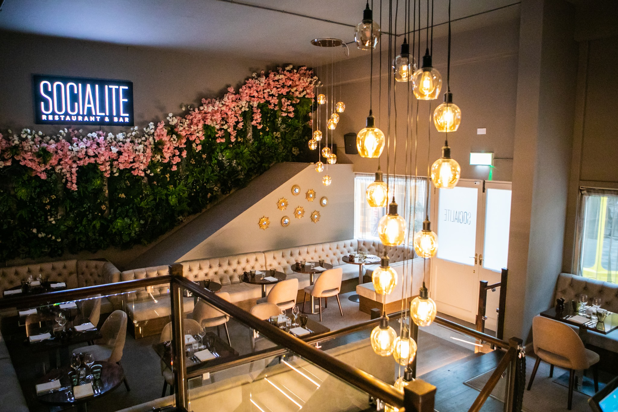 interior of socialite, decorative plants with pink flowers hanging on the wall, a white light logo attached to wall, white charis and brown tables, beautiful lights hanging of celiling