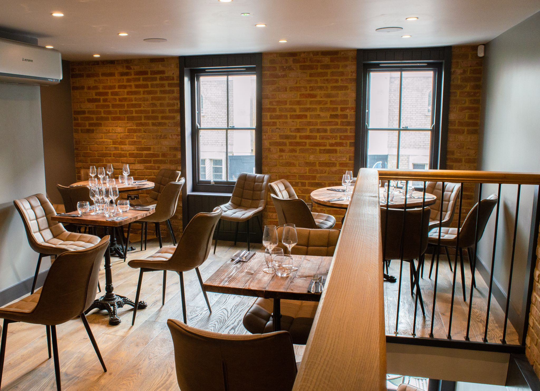 Upstairs At TEN Brighton. A redbrick wall looks out onto a street, wooden tables set with tableware and deep brown leather seats