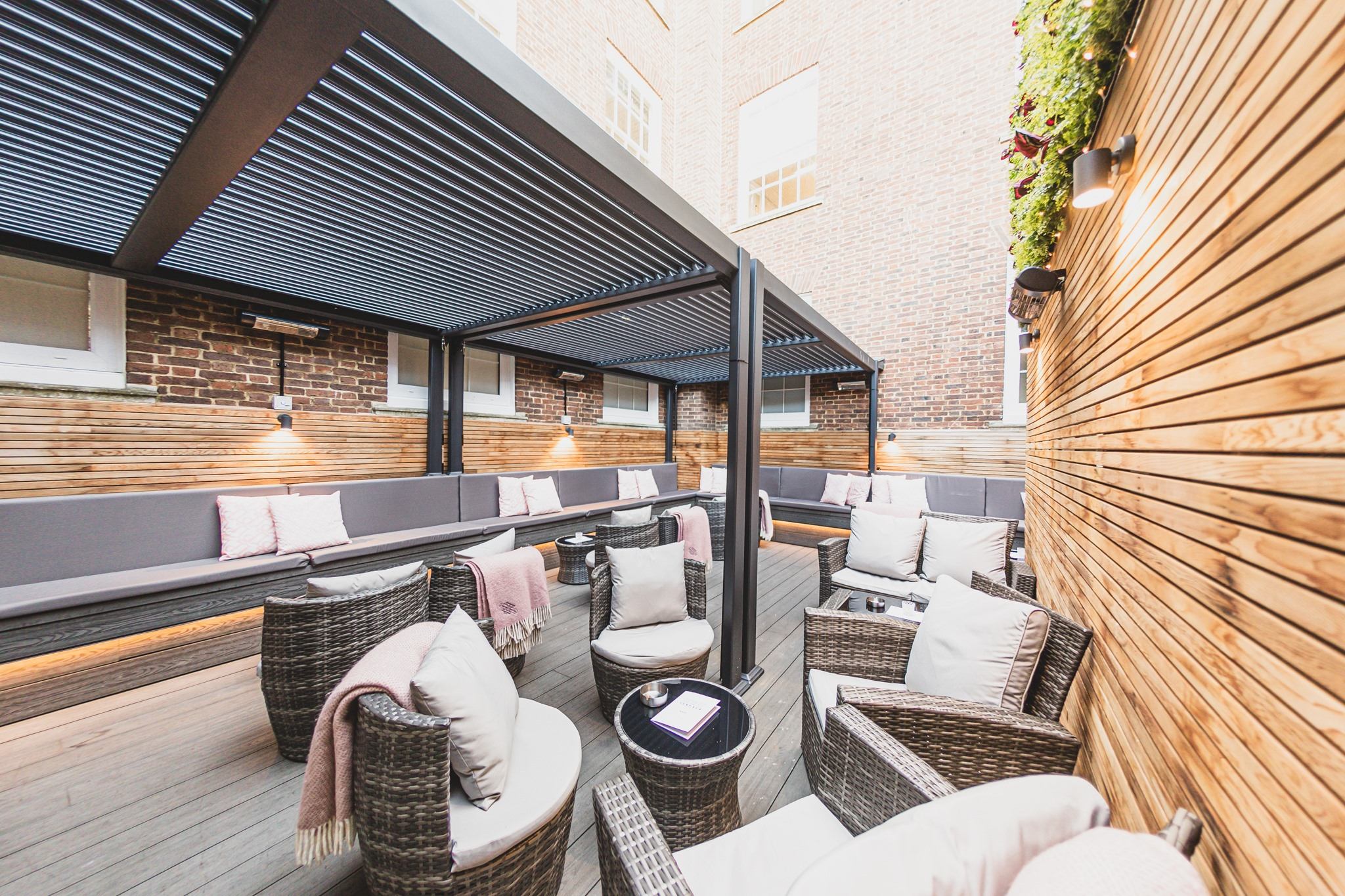 The roof terrace at Socialite Brighton, brown comfy chairs and sofas with white pillows and covers
