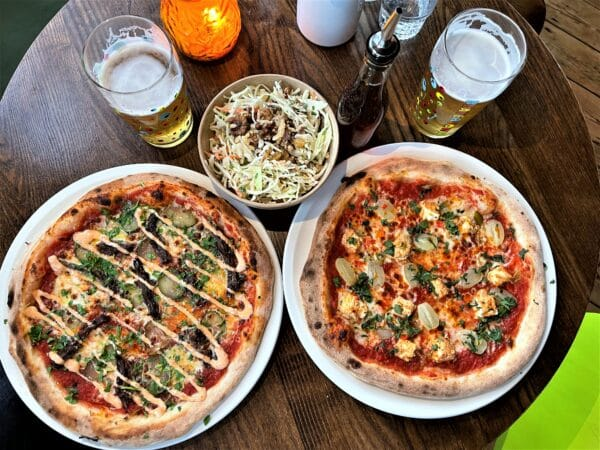 table laid out with two different types of pizzas two glasses of beer