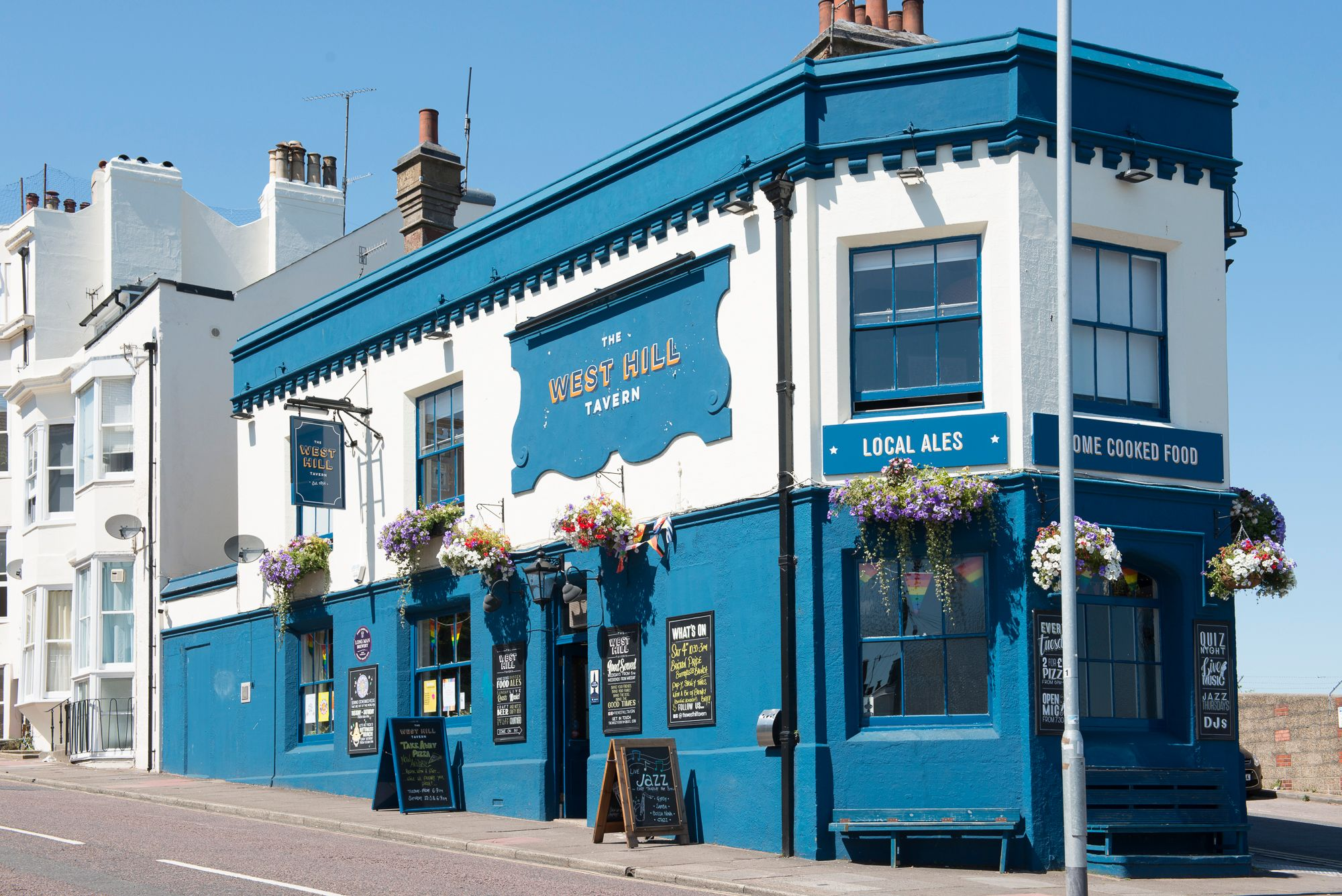 pub exterior. blue and white colored walls, flowers added as decoration