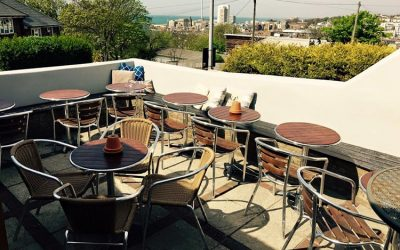 A sunny beer terrace with a view and tables.