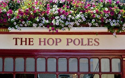 Exterior shot of The Hop Poles sign with summer flowers