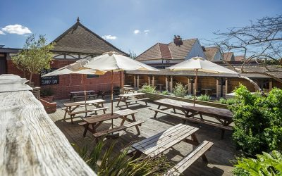 The Garden Bar on a sunny day with wooden tables and parasols.