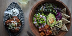 A colourful Buddha bowl with avocado and tofu along with a side of cauliflower wings