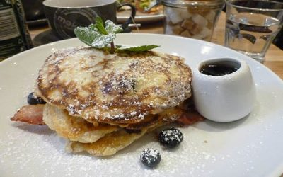 A plate of pancakes with blueberries and a sprig of mint
