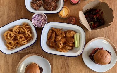 A selection of burgers, chicken wings, curly fries and dips photographed from above.