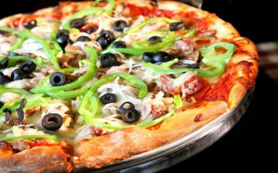 Close up photograph of an olive and green pepper pizza