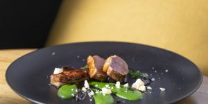 Small medallions of pork arranged on a plate with a green puree on a dark grey plate with a yellow background