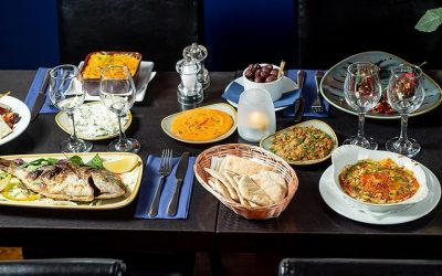 A feast of Greek food displayed on plates, bowls including a whole fish, dips and sides. Served on a black table with dark interiors.