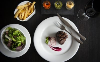 Steak dish with fries, sides and dips served on white dishes and a black table with a glass of red wine.