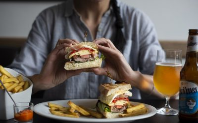 A person eating a beef burger that's been cut in half. Served on a white plate with fries and a glass of beer.