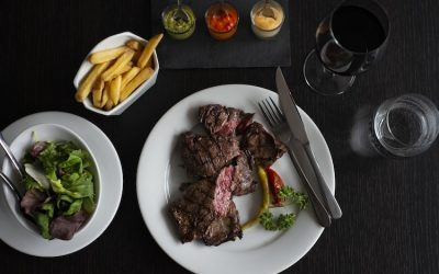 Steak and chips with three dipping sauces. Served on a dark surface with a glass of red wine.
