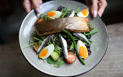 A fillet of fish sat on a bed of leafy salad with boiled eggs quartered. Served on a grey glazed ceramic plate.