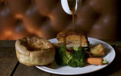 Roast pork with a Yorkshire pudding, broccoli, potatoes and gravy being poured over the dish