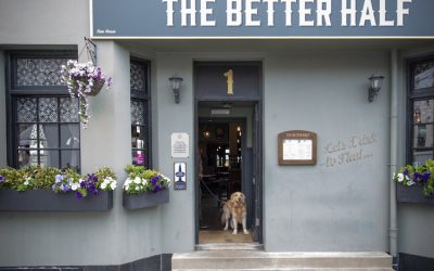 Exterior shot of the grey painted pub with hanging baskets and a dog in the doorway.