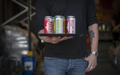 Cans of colourful craft beers served on a tray