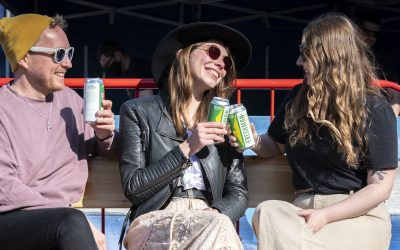 People enjoying cans of craft beer outside on a sunny day