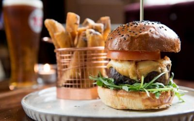 A giant beef burger stacked with sunflower shoots, tomato and cheese in a seeded bun. Served with a basket of chips and a pint of beer.