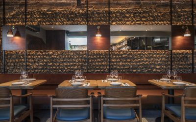 Interior of Burnt Orange restaurant with flint stone walls, wooden tables and soft lighting.