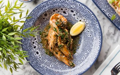 Whole prawns in a garlic sauce with a wedge of lemon served in a blue ceramic plate with a leafy plant displayed next to the plate.