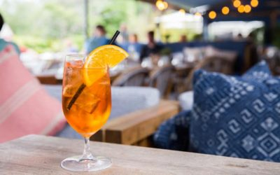 A glass of Aperol Spritz with a garnish for fresh orange sat on a table with a restaurant view in the background.