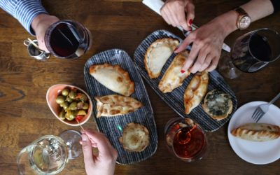 Overhead shot of wine and empanadas served on the dining table among friends sharing the tapas.