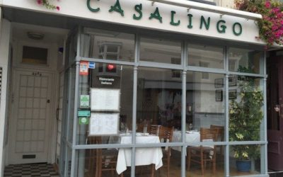 Restaurant exterior shot of Casalingo entrance and large window with hanging baskets.