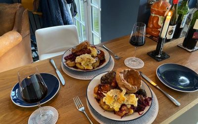 Plates of Sunday roasts at home served with seasonal veggies, roast potatoes, gravy & Yorkshire puddings.