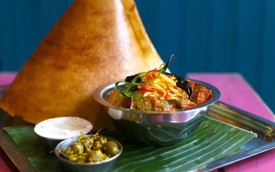 Colourful Indian food served on a leaf and in metal bowls.