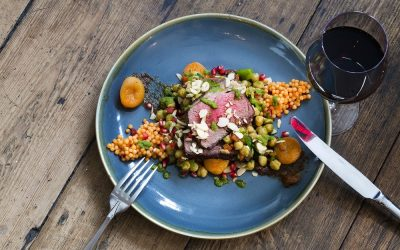 A blue ceramic plate with a bed of giant couscous, sliced rare meat, apricots and glass of red wine.