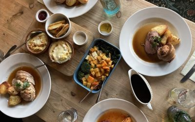 Roast dinners laid out on the table with a selection of sides and gravy
