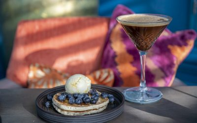 A stack of pancakes with blueberries and ice cream and an espresso martini, behind are some orange cushions