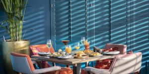 A table laid for Brunch at Cyan, with four orange chairs and beautiful light streaming through the blinds