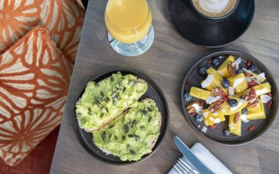 Overhead photograph of brunch dishes on a wooden table next to cushioned seating. A plate of avocado on toast and a fruit salad served with orange juice and a coffee.