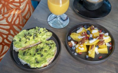 Smashed avocado on toast with a fruit salad and glass of juice